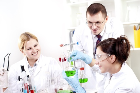 Chemists working with a team looking at the tube Stock Photo - 12328305