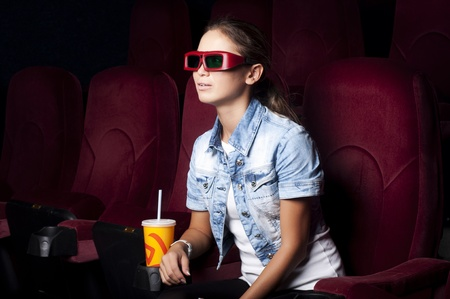 young woman sitting alone in the cinema and watching a movie photo