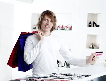 Young man at shopping mall checkout counter paying through credit card Stock Photo - 12596923