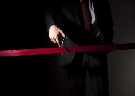 man in a suit, cuts a red tape, opening of event photo
