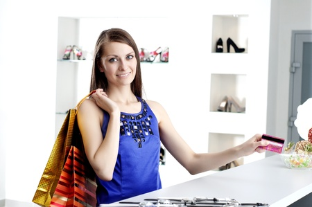 Young woman at shopping mall checkout counter paying through credit card Stock Photo - 12596931