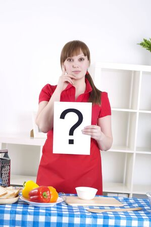 Young woman cooking fresh meal at home and holding question sign Stock Photo - 13089035