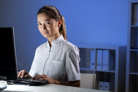 beautiful young woman doctor working at night in the office photo