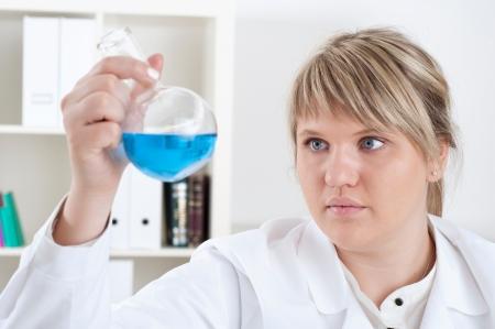 female chemist mixing liquids in test tubes photo