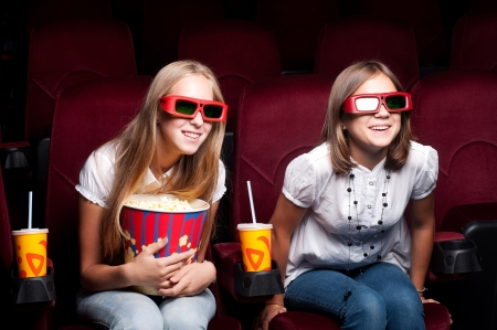 two beautiful girls watching a movie at the cinema photo