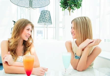 two beautiful girls, have a nice time, chatting in a cafe Stock Photo - 14737419