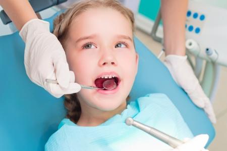 menina abriu a boca para verificar com um dentista, monitorar a sa