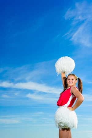 Young cheerleader in red costume with pampon photo