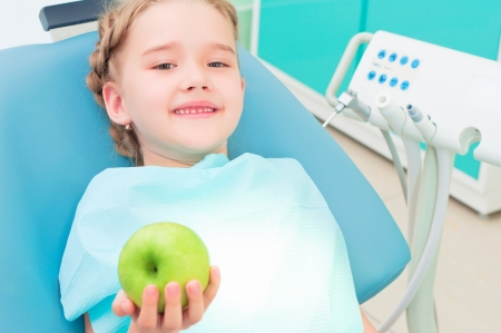 girl in the dentist s chair shows a green apple, regular care of your teeth photo