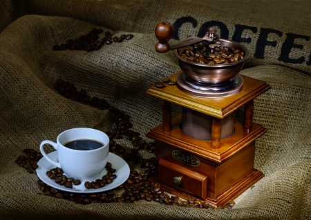 Coffee Mill with beans, cup and burlap  still life photo