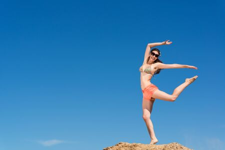 beautiful young woman jumping on a background of blue sky, having a fun time photo