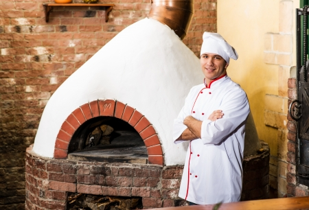 portrait of a cook in the kitchen near the wood-burning oven for pizzas, traditional cuisine photo