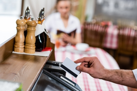 waiter inserts the card into a computer terminal, against visiting the restaurant photo