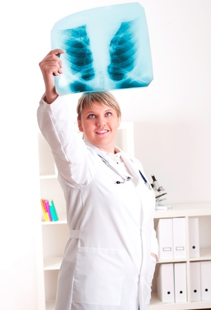 woman doctor looks at x-ray film, smile photo