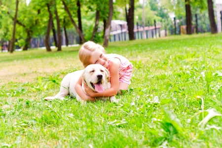 girl and she lablador, hugging in the park lying on the grass photo