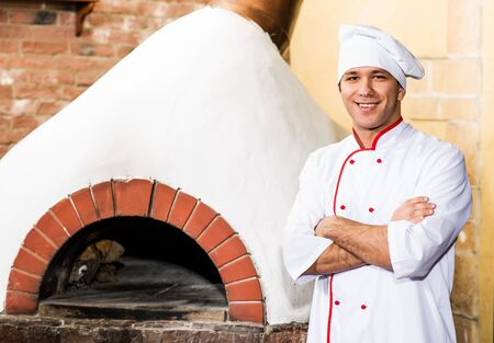 pizza oven: portrait of a cook in the kitchen near the wood-burning oven for pizzas, traditional cuisine Stock Photo