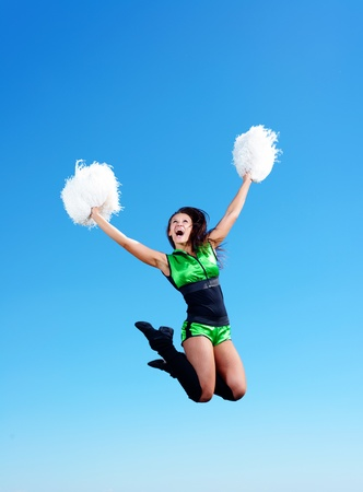 cheerleader girl jumping on a background of blue sky photo