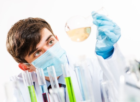 Portrait of a scientist working in the lab examines a test tube with liquid Stock Photo - 16588180