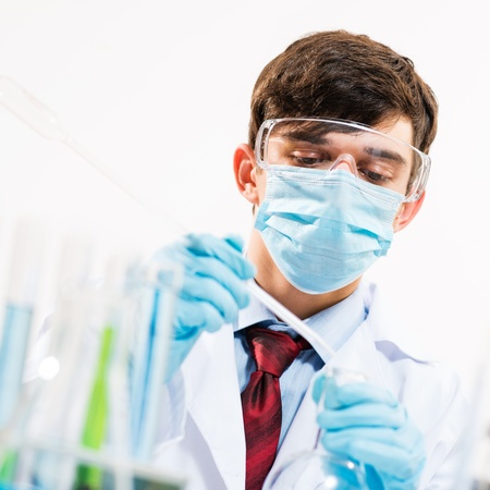 scientist working in the lab, in protective mask, examines a test tube with liquid Stock Photo - 16598935