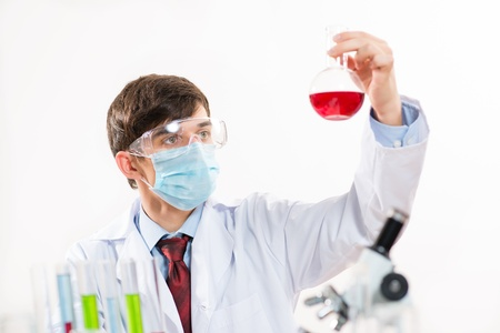scientist working in the lab, in protective mask, examines a test tube with liquid Stock Photo - 16669852