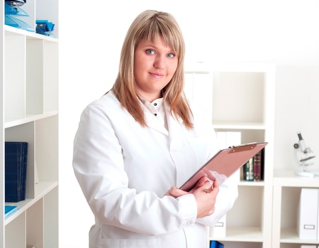 portrait of a young woman doctor with a clipboard, smiling photo