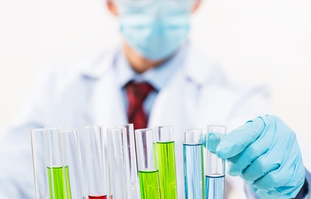 scientist working in the lab, in protective mask and cap, examines a test tube with liquid Stock Photo - 16720976