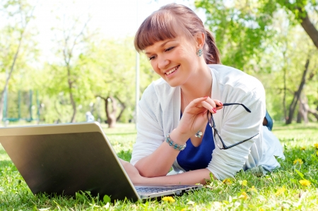portrait of a beautiful woman, working with a laptop in a park photo