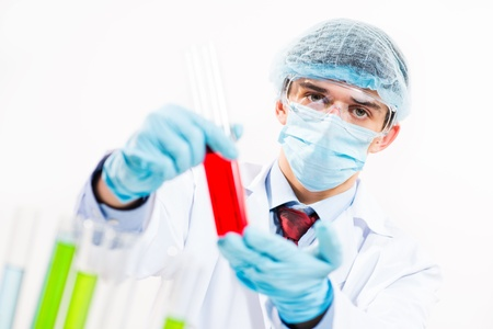 scientist working in the lab, in protective mask and cap, examines a test tube with liquid Stock Photo - 16753299