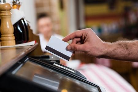 camarero: insertos camarero la tarjeta en una terminal de computadora, en contra de visitar el restaurante Foto de archivo