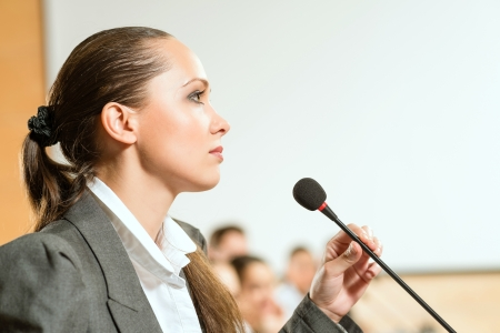 presenter: female speaker looks into the room and said into the microphone, speech at the conference