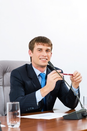 Portrait of a businessman sitting at a table and holding a pen photo