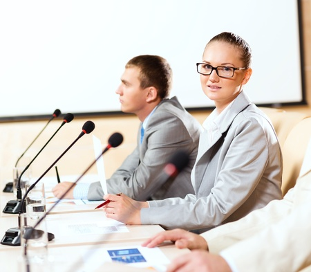 group of business people sitting at the tables at the presentation, woman looking at the camera Stock Photo - 16825853