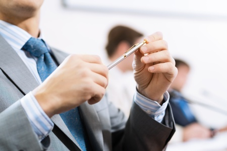 one on one meeting: businessman sitting at a table and holding a pen