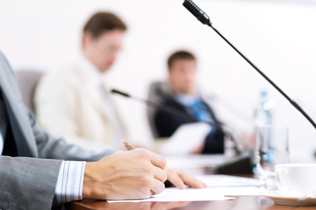 conventions: Businessman writing on paper notes, to communicate with colleagues in the background Stock Photo