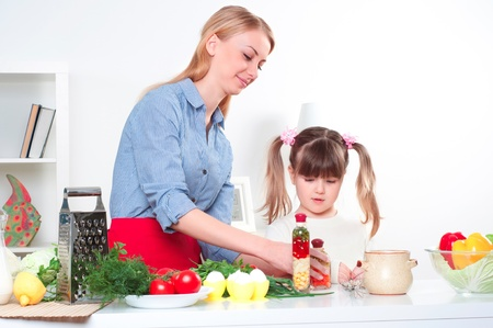 Mother and daughter cooking together, help children to parents Stock Photo - 16844759