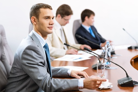 Portrait of a businessman, said into the microphone, in the background colleagues communicate with each other Stock Photo - 16881326