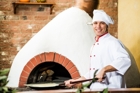 Chef puts dough in the oven for pizzas, traditional cooking photo