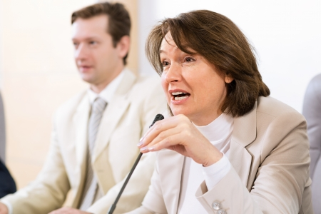 Portrait of a senior business woman bending speaks into the microphone Stock Photo - 16881285