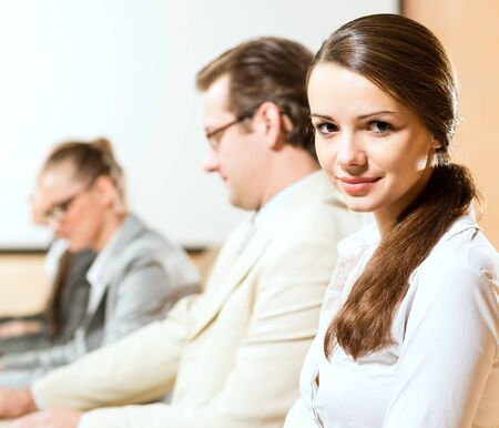group of business people sitting at the tables at the presentation, woman looking at the camera Stock Photo - 16890921