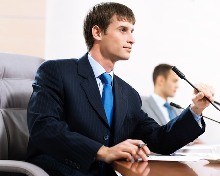 Portrait of a businessman, said into the microphone, in the background colleagues communicate with each other Stock Photo - 16902484