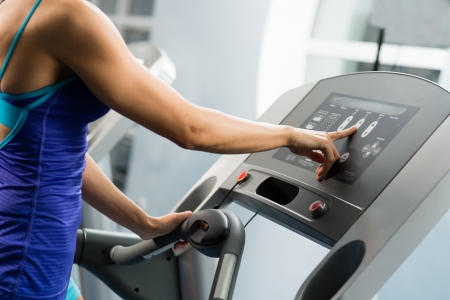 woman adjusts the treadmill at the beginning of training, do fitness in the sport club Stock Photo - 16935254