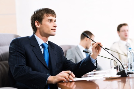 Portrait of a businessman, said into the microphone, in the background colleagues communicate with each other Stock Photo - 16935264