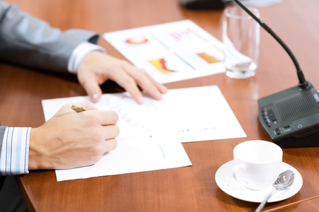 business deal: Businessman writing on paper notes, On the table is a cup of coffee and a device for communication at the conference Stock Photo
