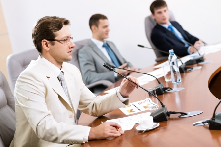 Portrait of a businessman, said into the microphone, in the background colleagues communicate with each other Stock Photo - 16960341