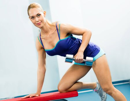 female athlete dumbbell, exercise in the fitness club photo