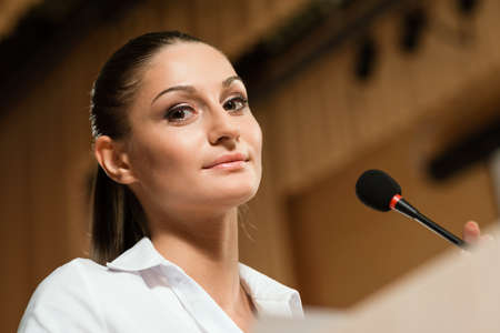 Portrait of a business woman holding a microphone and looks ahead Stock Photo - 16987035