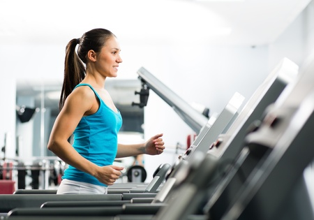 attractive young woman runs on a treadmill, is engaged in fitness sport club photo