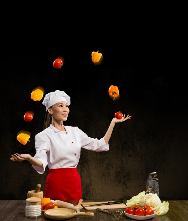 Asian woman chef juggling with vegetables, cooking skills photo
