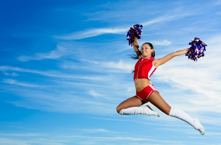 Young cheerleader in red costume jumping against blue sky Stock Photo
