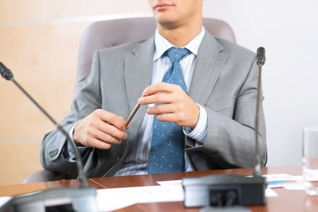 businessman sitting at a table and holding a pen Stock Photo - 17009710